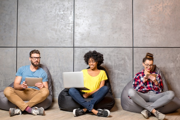 Multi ethnic coworkers dressed casually in colorful clothes working with different gadgets sitting on the bag chairs on the gray wall background
