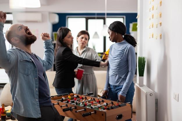多民族の同僚は、ビールのアルコールを飲みながら仕事の後にフーズボールゲームをします。テーブルでサッカーサッカーを楽しんだり、オフィスの楽しいパーティーで起業を祝ったりする友人