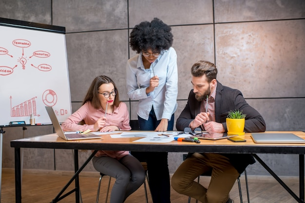 회색 벽 배경에 화이트보드가 있는 직장에서 문서 및 노트북과 함께 일하는 다민족 동료