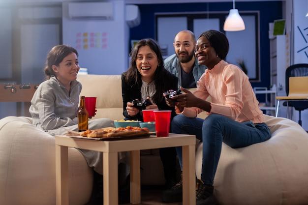 オフィスで働いた後、テレビコンソールで楽しいゲームをしている友人の多民族の多様なグループ。ソファの上で屋内でゲームをするためのジョイスティックコントローラーを持っている陽気な同僚。祝う幸せなチーム