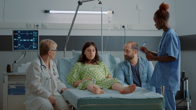 Multi ethnic doctor and nurse talking to pregnant woman