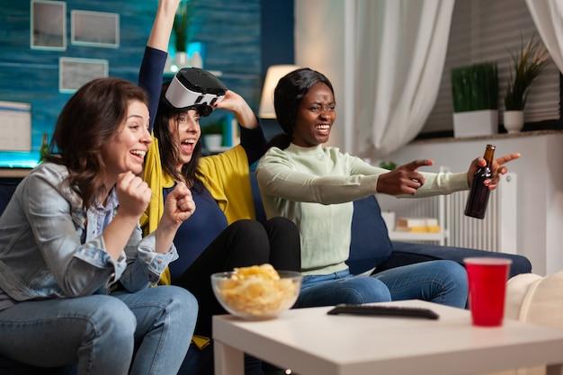 Многонациональный друг празднует победу, играя в видеоигры в виртуальной реальности. группа людей смешанной расы гуляет вместе, развлекаясь поздно ночью в гостиной.