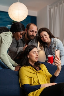 Multi ethnic friends bonding and talking on smartphone during video call in home living room. group of multiracial people spending time together sitting on couch late at night in living room.