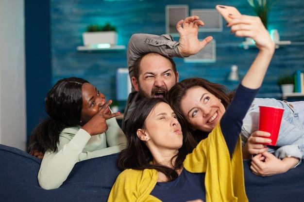 Amici multietnici che si legano insieme scattano foto e pubblicano espressioni diverse sui social media