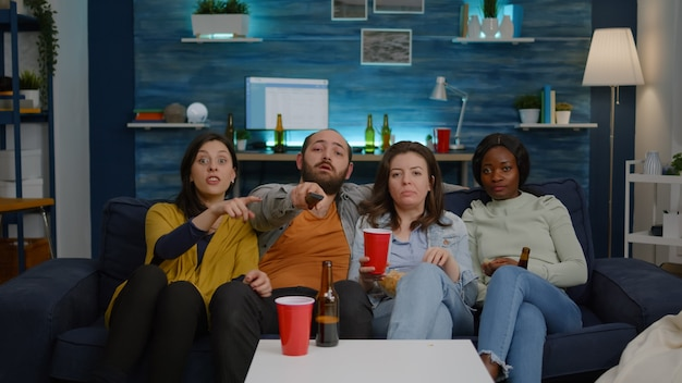 Multi-ethnic friends changing channel using remote on television until find comedy movie late at night sitting on sofa during home cinema party. group of multiracial people enjoying time together