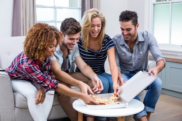 Multi ethnic friends enjoying pizza at home