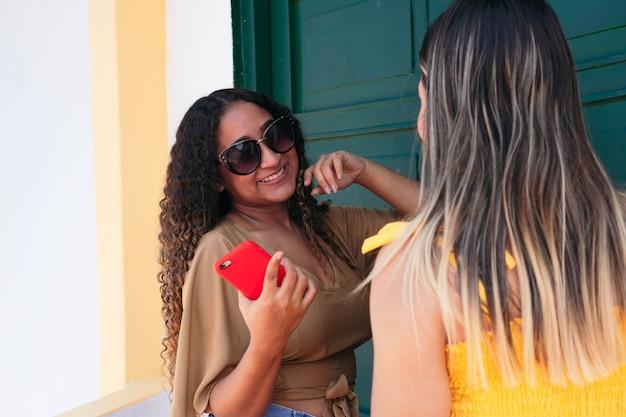 Многонациональные друзья наслаждаются улицей на открытом воздухе. латинская девушка смеется с другом