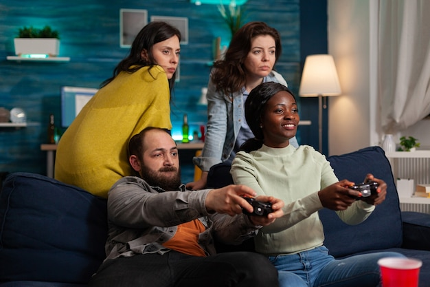 Multi ethnic friends feeling good during oline games challange using wireless controller. mixed race group of people hanging out together having fun late at night in living room.