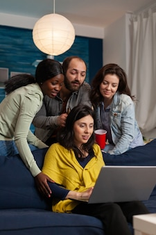 Multi ethnic friends hanging out talking on webcam laptop during video call. group of multiracial people spending time together sitting on couch late at night in living room.