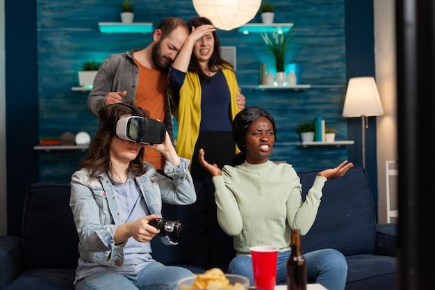 Многонациональные друзья проигрывают соревнованиям по онлайн-видеоиграм и переживают виртуальную реальность с помощью гарнитуры. группа людей смешанной расы гуляет вместе, развлекаясь поздно ночью в гостиной.