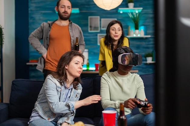 Друзья из разных национальностей общаются, играют в видеоигры, переживают виртуальную реальность с помощью гарнитуры. группа людей смешанной расы гуляет вместе, развлекаясь поздно ночью в гостиной.