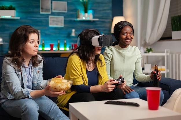 Многонациональные друзья общаются, играют в видеоигры в очках vr, пьют пиво, сидя на диване. группа людей смешанной расы гуляет вместе, развлекаясь поздно ночью в гостиной.