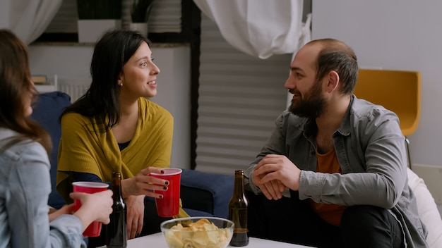 夜のホームパーティーで、リビングルームのソファで休んでビールを飲みながら交流する多民族の友人たち。一緒に過ごす時間を楽しんでぶらぶらしている多民族の人々のグループ