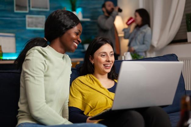 소파에 앉아 노트북으로 재미있는 온라인 비디오를 보면서 사교 활동을 하는 다민족 친구들. 배경에서 맥주를 마시는 두 여성은 엔터테인먼트 파티에서 함께 시간을 보냅니다.