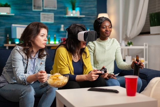 Многонациональные друзья, использующие гарнитуру виртуальной реальности во время соревнований по играм, сидя на диване, афроамериканская женщина пьет пиво. группа людей смешанной расы, гуляющие вместе, развлекаясь допоздна