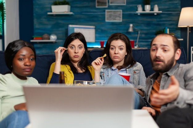 다민족 친구들이 함께 소파에 앉아 노트북 컴퓨터로 온라인 영화를 보고 있습니다. 다인종 사람들이 어울리고, 맥주를 마시고, 늦은 밤 거실에서 간식을 먹습니다.