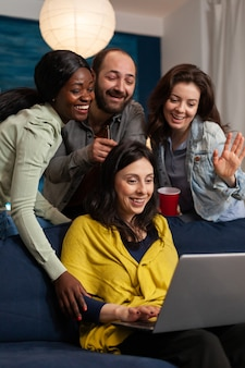Multi ethnic friends waving at laptop webcam during video call sitting on couch late at night. group of multiracial people spending time together sitting on couch late at night in living room.