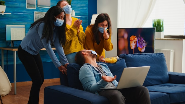 Multi ethnic friends wearing face mask eating snacks using laptop keeping social distancing to prevent coronavirus spread during global pandemic having fun in home living room. conceptual image.