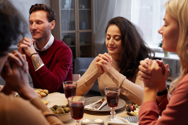 Multi-ethnic group of adult people praying at thanksgiving dinner with friends and family