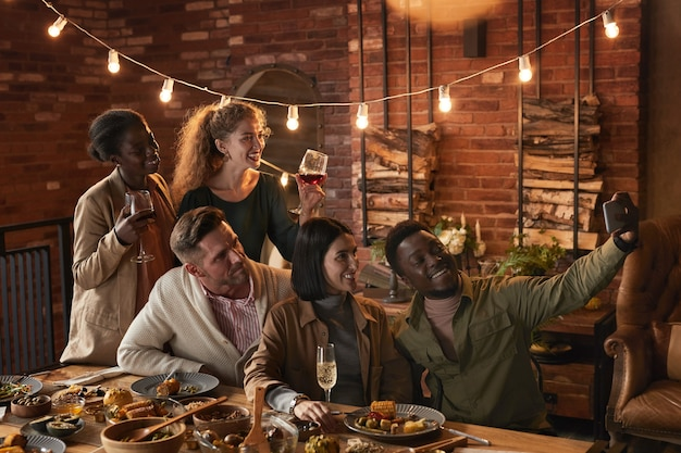 Multi-ethnic group of cheerful adult people taking selfie photo while enjoying party with outdoor lighting