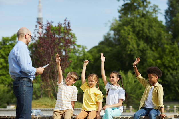 Multi-ethnic group of cheerful kids raising hands and listening to male teacher while enjoying outdoor lesson in sunlight, copy space