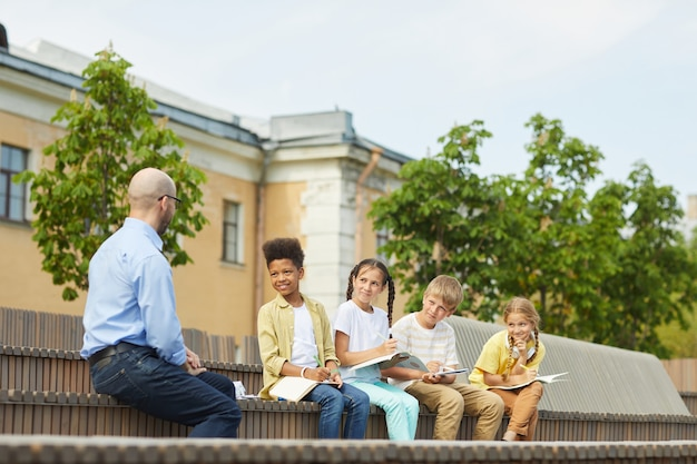 Multi-ethnic group of children listening to male teacher while sitting on bench and enjoying outdoor lesson in sunlight, copy space