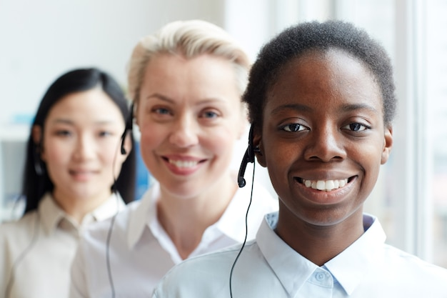 Multi-ethnic group of female call center operators looking standing in row, focus on smiling african-american woman wearing headset in foreground