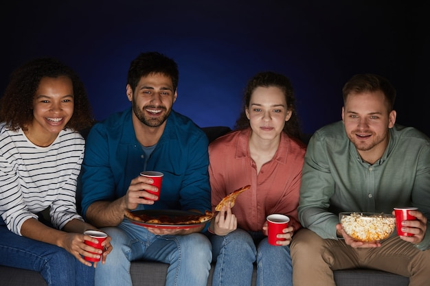 Multi-ethnic group of friends watching movies at home while eating snacks and popcorn sitting on big sofa in dark room