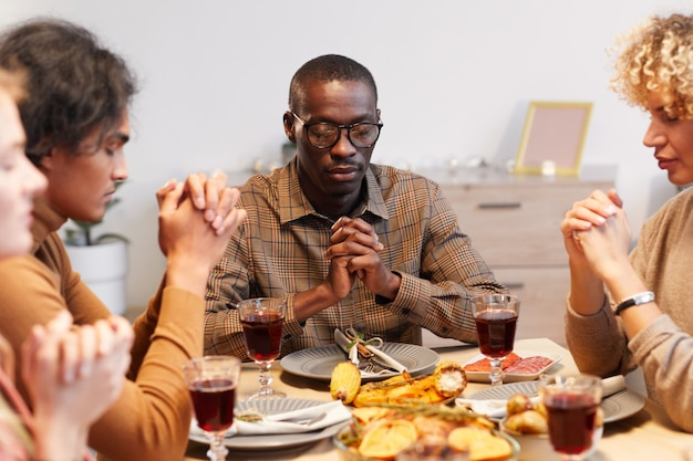 Multi-ethnic group of modern adult people praying with eyes closed while enjoying thanksgiving dinner with friends and family