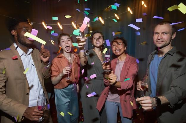 屋内でパーティーを楽しみながら紙吹雪で踊るのんきな人々の多民族グループ、フラッシュで撮影