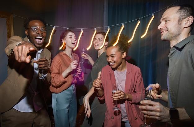 家でパーティーを楽しみながら踊るのんきな人々の多民族グループ、フラッシュで撮影