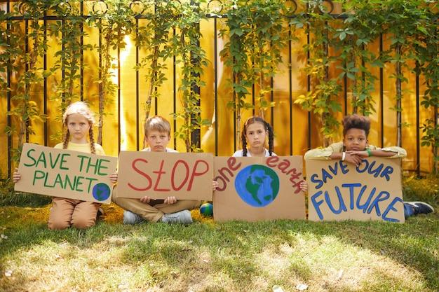 Save the planetの看板を掲げ、屋外の芝生に座って自然に抗議しながらカメラを見ている多民族の子供たち、コピースペース
