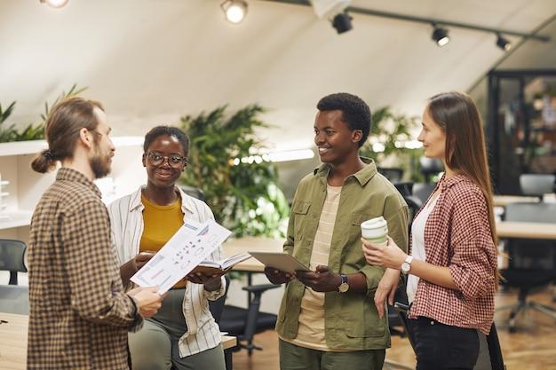 현대 사무실에서 원 안에 서서 유쾌하게 웃고있는 동안 작업 프로젝트에 협력하는 현대 젊은이들의 다민족 그룹