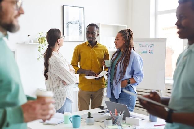 회의실에서 휴식 시간 동안 채팅 창의적인 사업 사람들의 다민족 그룹