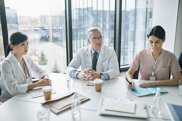 의료 세미나 중 회의실의 회의 테이블에 앉아 있는 다민족 의사 그룹, 복사 공간