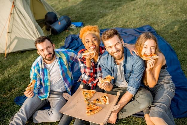캠핑에서 야외 레크리에이션을 하는 동안 캐주얼하게 옷을 입고 즐겁게 피자를 먹는 다민족 그룹