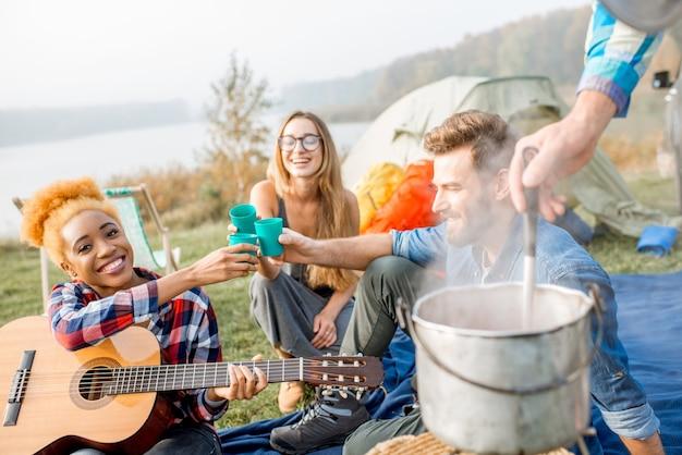 キャンプでの屋外での夕食時に、カジュアルにチリンと鳴るメガネを着た友人の多民族グループ