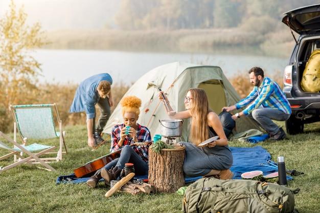 湖の近くの屋外レクリエーション中に、ピクニックをしたり、大釜でスープを調理したりして、カジュアルな服を着た友人の多民族グループ