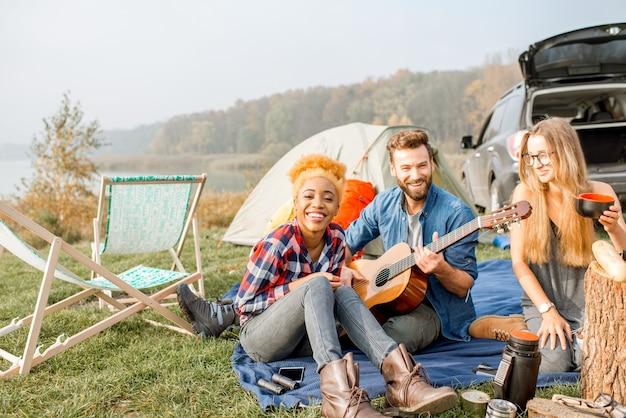 캐주얼하게 옷을 입은 여러 민족 친구들이 피크닉을 하고, 가마솥으로 수프를 요리하고, 호수 근처에서 야외 레크리에이션을 하는 동안 기타를 연주합니다.