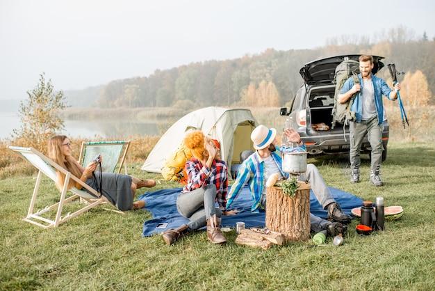 호수 근처에서 텐트, 자동차, 하이킹 장비를 갖추고 야외 레크리에이션을 하는 동안 캐주얼하게 옷을 입은 다민족 친구들
