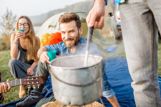 キャンプでのピクニック中に大釜で調理されたスープでおいしい夕食を食べているカジュアルな服を着た友人の多民族グループ