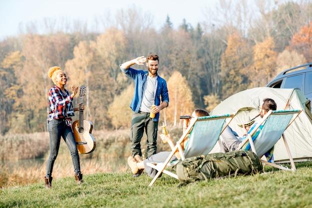 Многонациональная группа друзей, одетых в повседневную одежду, веселится во время отдыха на природе в кемпинге у озера