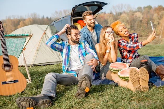 Многонациональная группа друзей, одетых в повседневную одежду, веселится, делая селфи вместе во время отдыха на природе с палаткой, автомобилем и походным снаряжением возле озера