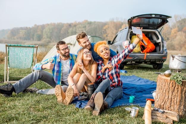 湖の近くでテント、車、ハイキング用品を使って屋外レクリエーション中に一緒にセルフィー写真を作るのを楽しんでいるカジュアルな服を着た友人の多民族グループ