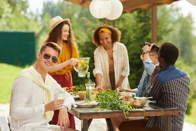 夏の屋外テラスで夕食を楽しんでいる友人の多民族グループ、笑顔のサングラスをかけている若い男に焦点を当てる