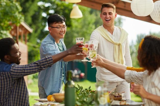 夏のパーティーで屋外で夕食を楽しんでいる友人の多民族グループは、テーブルのそばに立っている間、メガネをチリンと鳴らす2人の男性に焦点を当てます