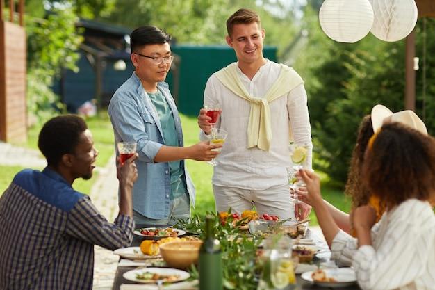 夏のパーティーで屋外で夕食を楽しんでいる友人の多民族グループ、テーブルのそばに立っている間乾杯する2人の男性に焦点を当てる