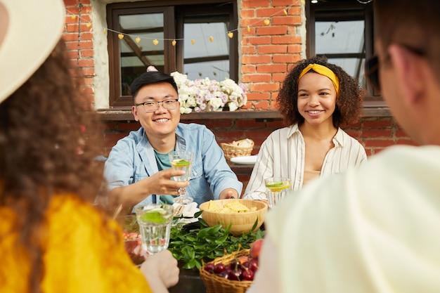 オープンテラスのテーブルに座って屋外で一緒に夕食を楽しんでいる友人の多民族グループ