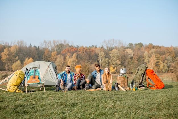 다민족 친구들이 피크닉을 하고, 피자를 먹고, 숲 근처에 텐트와 하이킹 장비가 있는 캠핑장에 나란히 앉아 있습니다.