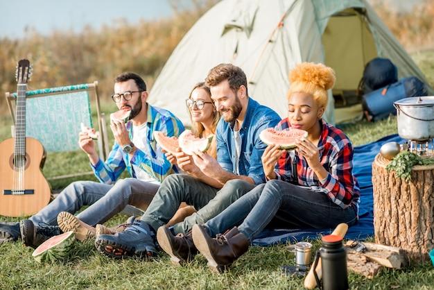 피크닉을 하는 다민족 친구들, 호수 근처에서 텐트, 자동차, 하이킹 장비를 갖춘 야외 레크리에이션 동안 수박을 먹습니다.
